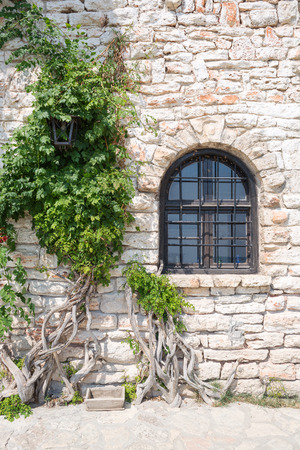 Old wooden window on stonewall, Balchik, Bulgaria