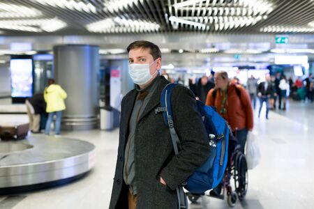 Young European man in gray coat, protective disposable medical mask in airport. Afraid of dangerous N-CoV 2019 influenza coronavirus mutated and spreading in China. Blue backpack, suitcase on wheels.