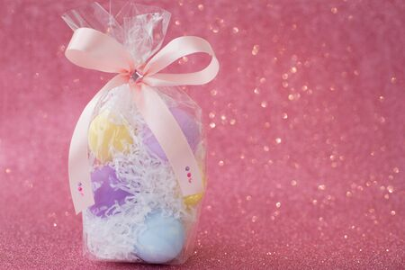 Multi-colored purple, pink, blue, yellow Easter eggs in a transparent gift package, decorated with a bow and rhinestones, on a pink shiny bokeh background. Symbol of celebration of religious holiday.