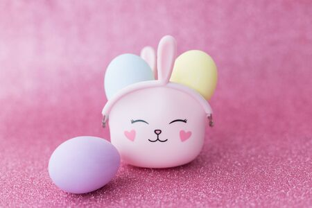 Easter bunny bag with eyes, nose, mouth with colorful eggs: purple, yellow and blue on a pink sparkling background. The hare is a symbol of a religious holiday and Catholics, Orthodox and Protestants.