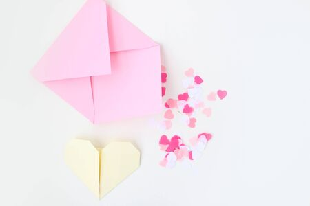 Flat lay: pink hand made envelope, confetti hearts, origami yellow heart made of paper for notes. Making postcard for Valentine's Day. Do it yourself. Photo from the series