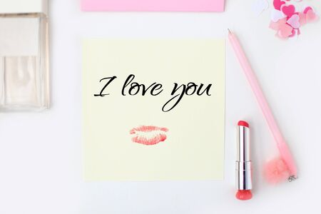 Flat lay: yellow paper, pink envelope, pen, pompom, perfume, lipstick, confetti hearts, lip print, i love you text. Making postcard in envelope for Valentine's Day.Do it yourself.Photo from the series 写真素材