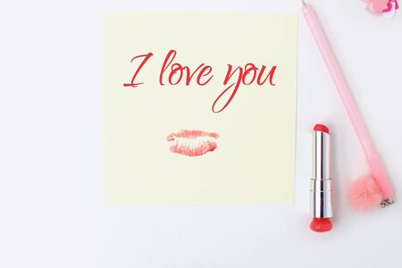 Flat lay: yellow paper, pink pen, pompom, lipstick, confetti hearts, lip print, i love you text. Making postcard in envelope for Valentine's Day.Do it yourself.Photo from the series