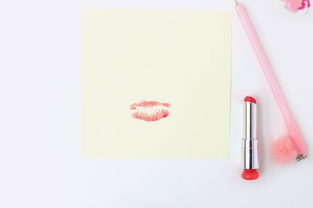 Flat lay: yellow paper, pink pen with pompom, lipstick, confetti hearts, lip print. Making postcard in envelope for Valentine's Day. Do it yourself. Photo from the series 写真素材