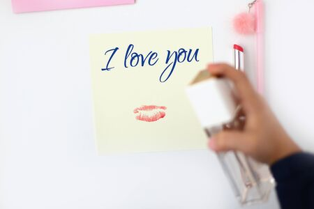 Paper note with lipstick print and text I love you. A bottle of pink perfume in hand. Pen with pompom. Making postcard in envelope for Valentine's Day. Do it yourself. Photo from the series