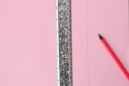 Flat lay: pink paper with a straight line drawn in pencil, silver ruler. Making a postcard in an envelope for Valentine's Day. Do it yourself. Photo from the series.