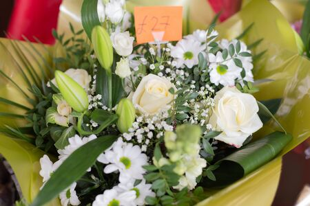 Bouquet of white flowers roses, lilies, gypsophila, chrysanthemums in the shop. Retail street sale near metro station for Valentine's Day on February 14 or International Women's Day on March 8.