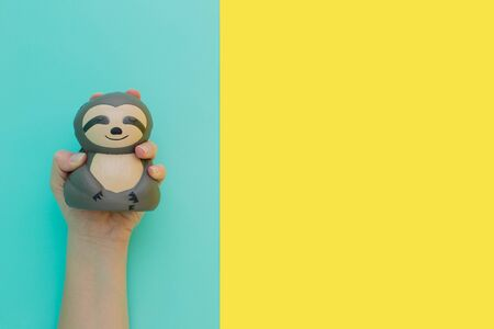 Flat lay antistress toy squish gray sloth squeezed in hand.Bright yellow blue background.Compressing, soft, squeezable items to relieve stress, problems, anxieties, worries.Summer concept.