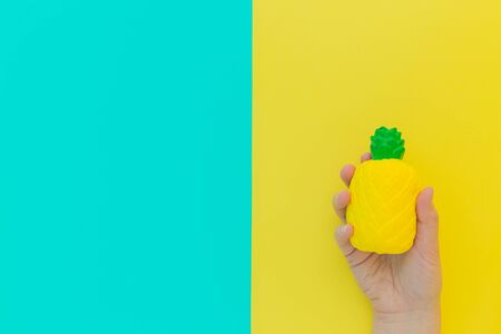 Flat lay antistress toy squish yellow pineapple with green leaves in hand.Bright blue background.Compressing, soft, squeezable items to relieve stress, problems, anxieties, worries. Summer concept.