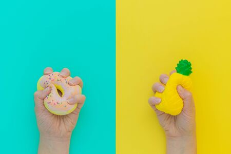 Flat lay antistress squish toys yellow pineapple,pink donut with sprinkles in hands.Bright blue background.Compressing,soft,squeezable items to relieve stress,problem,anxieties,worries.Summer concept.