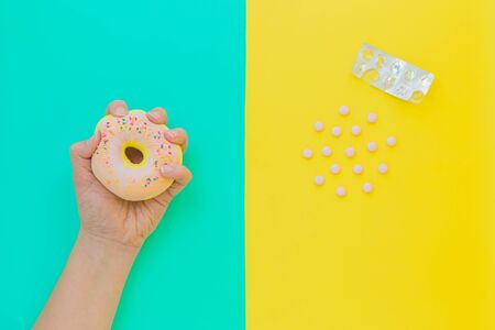 Flat lay antistress toy squish pink donut with sprinkles in hand, tablets, pills, blister.Bright blue yellow background.Compressing,soft,squeezable items to relieve stress,problems,anxieties,worries.