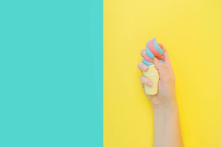 Flat lay antistress toy squish ice cream in waffle cone squezzed in hand.Bright blue yellow background.Compressing,soft,squeezable items to relieve stress,problems,anxieties,worries.Summer concept.