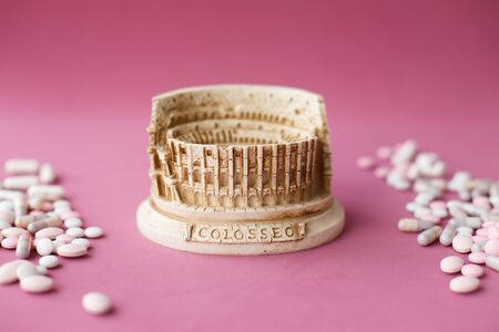 Stone statuette of the Coliseum building in Rome in Italy, surrounded by a bunch of antiviral pills and tables. Concept of dangerous infection with the Chinese coronavirus covid-2019. Pink background.