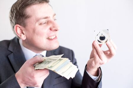 Nervous businessman in suit holds in hands drop of black oil of Brent brand and pack of dollars, screams,shouts.Crisis in financial market, falling and rising prices, quotes, changes in exchange rate.