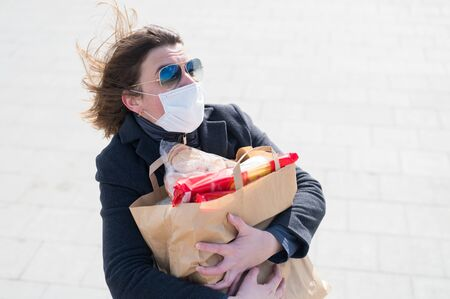 Scared woman in protective face mask,gray coat.Making store of food in craft bag before isolation:toilet paper,paste,cookies.Lack of products.Leaving city during quarantine of coronavirus covid-2019. Banque d'images