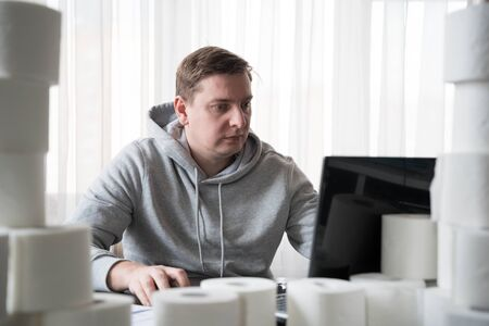 Young man in sports hoody switched to telework due to quarantine of coronovirus pandemic COVID-2019. Remote work at home table with toilet paper. Communication with boss by laptop. Online conference.