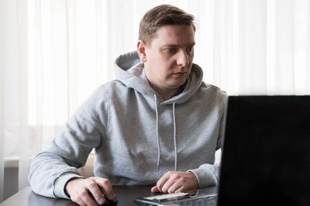 Young man switched to telework due to quarantine of coronovirus pandemic COVID-2019. Remote work at home table in sportswear. Communication with boss,colleagues through laptop. Online conference.