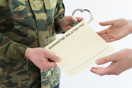 Police officer with handcuffs in khaki colored uniform stops people on the street for violating rules of quarantine of home self-isolation due to coronovirus covid-19 flu pandemic.Yellow fine receipt. Stock Photo