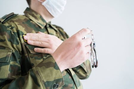 Police officer with face mask and handcuffs in khaki colored uniform stops, arrest criminal on the street for violating rules of quarantine of home self-isolation due to coronovirus covid-19 pandemic.
