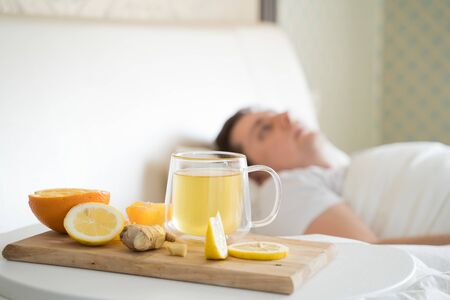 Cup with antipyretic drugs for colds,flu.Sick man in bed. Tea with citrus vitamin C,ginger root,lemon,orange.Wooden tray. Home self-treatment.Medical quarantine antiviral covid-19 coronavirus therapy. Foto de archivo