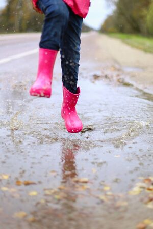 Happy little girl in pink waterproof jacket, rubber boots cheerfully jumps through puddles on street road in rainy weather. Spring, autumn. Children's fun in fresh air after rain. Outdoors recreation. Archivio Fotografico