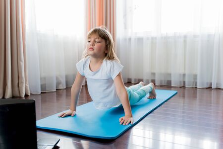 Little girl make home online laptop workout in flat.Baby yoga,fitness training.Distance school physical morning exercises on blue mat.Healthy activity,fun.Quarantine,coronavirus,covid-19.No equipment.