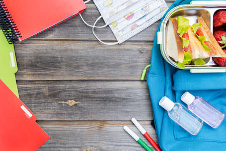 Kid's face mask, lunchbox with sandwiches, strawberries, bottles of sanitizer. Blue backpack with notebooks, pens, box on wooden background. Back to school. Lunch with safety precautions after coronavirus.