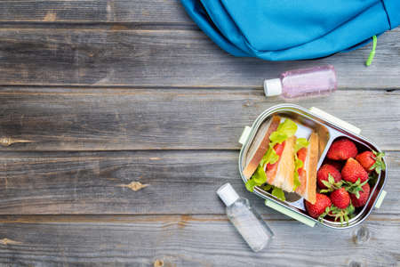 Lunchbox with sandwiches, fresh strawberries, two bottles of sanitizer and blue backpack on wooden background. Back to school after quarantine. Lunch break, box with safety precautions after coronavirus.