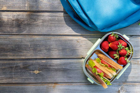 Lunchbox with sandwiches, fresh strawberries, blue chinldren's backpack on wooden bench background. Back to school after quarantine. Lunch break, box with fresh berries. Mom's care for kid's health. Zdjęcie Seryjne