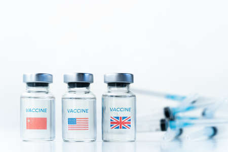 Transparent vials with USA, UK, China flag. Vaccine, syringe for covid-19 coronavirus, flu, infectious diseases. Injection after clinical trials for vaccination of human, people.Medicine, drug concept.