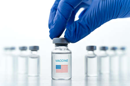 Transparent vials with USA, american flag. Vaccine for covid-19 coronavirus, flu, infectious diseases. Hand in glove. Injection after clinical trials for vaccination of human, people.Medicine, drug concept.