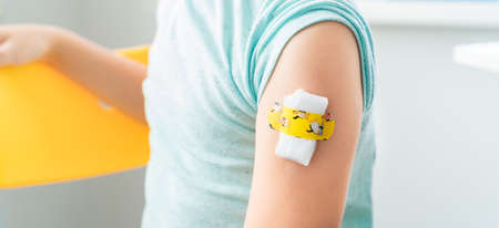 Vaccination of little girl in doctor's office.Kids funny adhesive plaster, gauze napkin.Sits on chair.Vaccine for covid-19 coronavirus, flu, infectious diseases.Injection.Clinical trials for human, child.