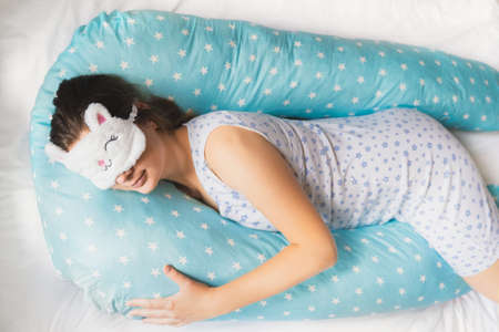 Pregnant woman sleeps in nightgown in bed on blue comfortable supporting pillow with stars. Funny sleeping white mask in form of bunny, cat with eyes, ears, mouth. Accessories for expectant mothers. Stock Photo