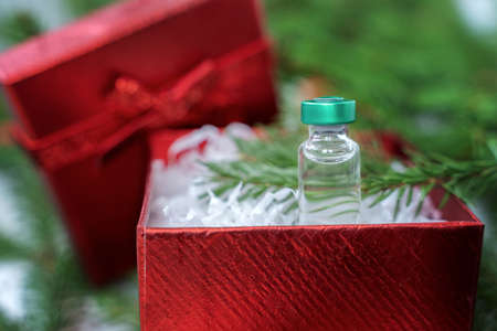 Best gift for Christmas. Vial with new tested vaccine for covid-19 coronavirus, dangerous flu, infection. Small red holiday box with bow. Green branches of new year tree, decorations. White plaid.