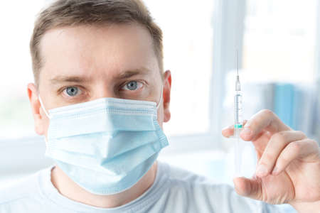 Man, adult in face mask in doctor's office is vaccinated. Syringe with vaccine for covid-19 coronavirus, flu, dangerous infectious diseases. Injection after clinical trials for human, child. Medicine.