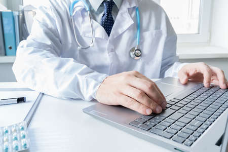 Doctor types, speaks, talks to patient by laptop. Telehealth, telemedicine, online consultation, video call conference, Medical concept, Caucasian man, blue eyes, white robe, stethoscope, Coronavirus covid-19.