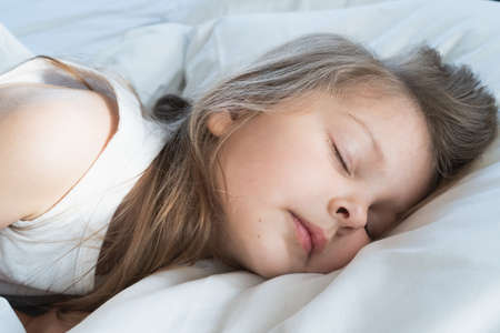 Little girl sleeps on pillow in bed with closed eyes. Evening late going to bed by mom. Early morning wake up, rise to kindergarten, school. Bedtime, sweet dreams. Kids correct daily routine for child. Banque d'images