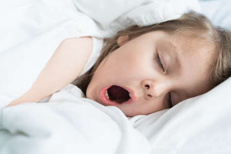 Little snoring girl, sleeping on pillow in bed with closed eyes. Evening late going to bed. Early morning wake up, rise to kindergarten, school.Bedtime, sweet dreams.Kids correct daily routine for child. Banque d'images