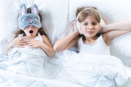 Little girls sleep in bed. One is snoring hard, sister is plugging ears with fur headphones. Early morning wake up, rise to kindergarten, school. Bedtime, sweet dreams.Kids correct daily routine for child. Archivio Fotografico