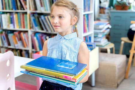 Little girl holds stack of books with fairy tales in children's library. Special reading kids room. Shelves with bright interesting, educational books about animals.Table, chair. Standard-Bild