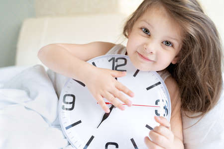 Little sleeping girl with big, huge clock in hands. Early morning wake up before kindergaten, school. White pillow, blanket in bed. Sleepy child. Sweet dreams. Bedtime. Correct mode of children's rest. Archivio Fotografico