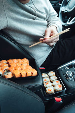 Man is eating sushi, Philadelphia rolls with fish, rice, salmon, cream cheese, avocado in car. Fast, safe, takeaway food on the road to coronavirus pandemic. Delicious japanese snacks with chopsticks.