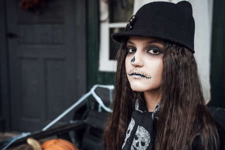 Beautiful scary little girl celebrating halloween. Terrifying black, white half-face makeup and witch costume, stylish image. Horror, fun at children's party in barn on street. Hat, fur coat, chain.