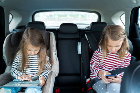 Little girls, sisters are driving in car, children play video games in tablet and mobile phone. Traveling on road in safe baby seats with child belts. Fun family trip, activity with parents.