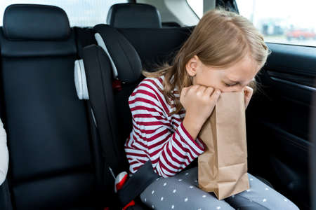 Little girl is driving in car. Kid is sick, feels bad and vomiting into paper bag. Traveling, riding on road in safe baby seats with child belts. Fun family trip, activity with parents.