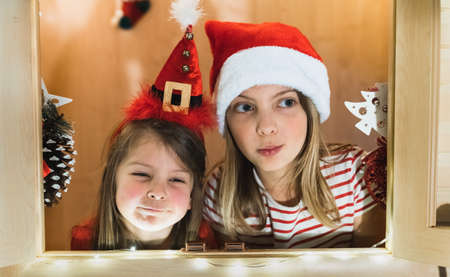 Two happy little girls, sisters are playing in children's playhouse with windows. Preparing for Christmas and New Year. Garlands, santa claus and elf hats, gifts, decorations. Greetings, celebration.