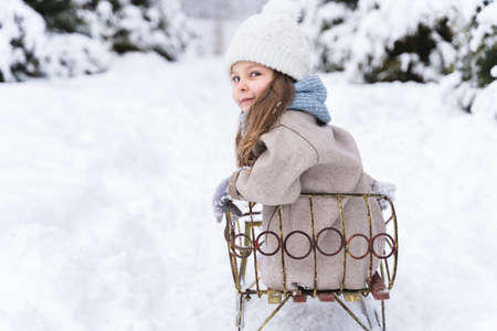 Little beautiful stylish girl sledding with sister. Winter hat, woolen coat, blue scarf, snood. Kids walking, playing in forest,park among trees covered with snow.Country house yard.Fashionable image.