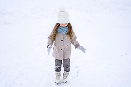 Beautiful little cute girl learn to skate on ice skating rink in park. Fall down and have fun. Stylish look, warm woolen coat, white hat, scarf, snood. Winter family activities, sport, games outdoors.
