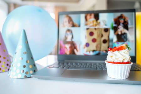 Kids virtual birthday home party. Strawberry cupcake. Online conference,video call in laptop computer. Friends on screen,greetings. Decoration, gifts,balloons,flags,caps.Children celebrate holiday