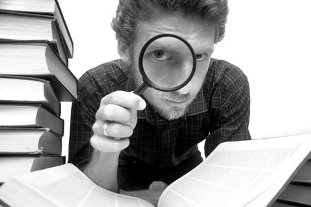 Man sitting amongst books with a magnifier Stock Photo - 2346259